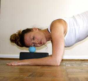 Relieve jaw and head tension with a Yoga Tune Up® Therapy ball on your temple.