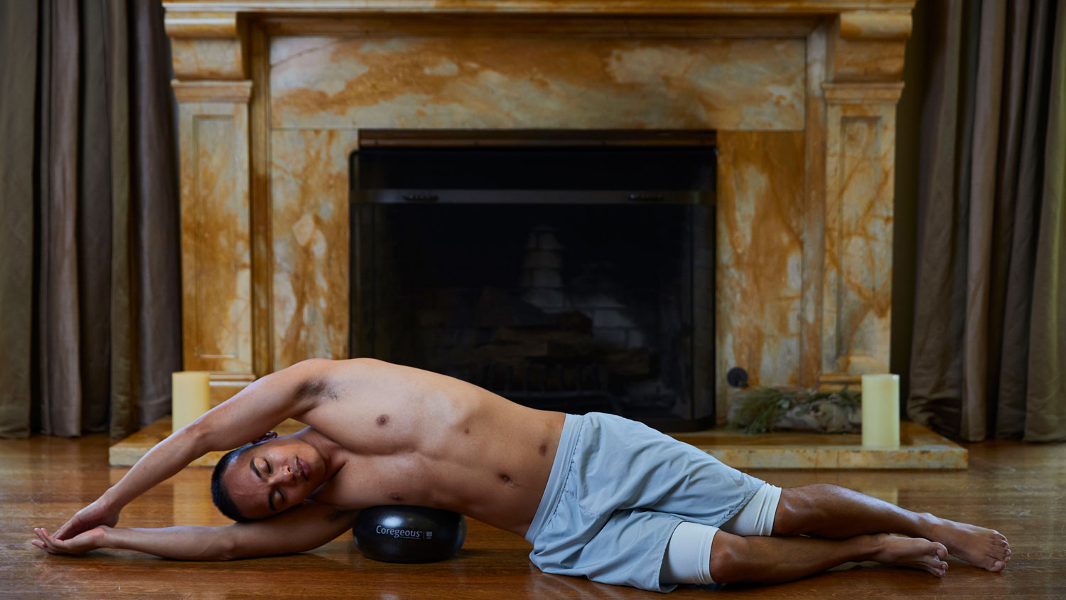 Yoga Tune Up Teacher Mike Berina lays on his side with the Coregeous ball tucked within his waist to encourage self-massage the muscles of the respiratory system.