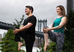 Dr. Erich Anderer and Ariel Kiley in a standing knee to chest pose in Brooklyn New York