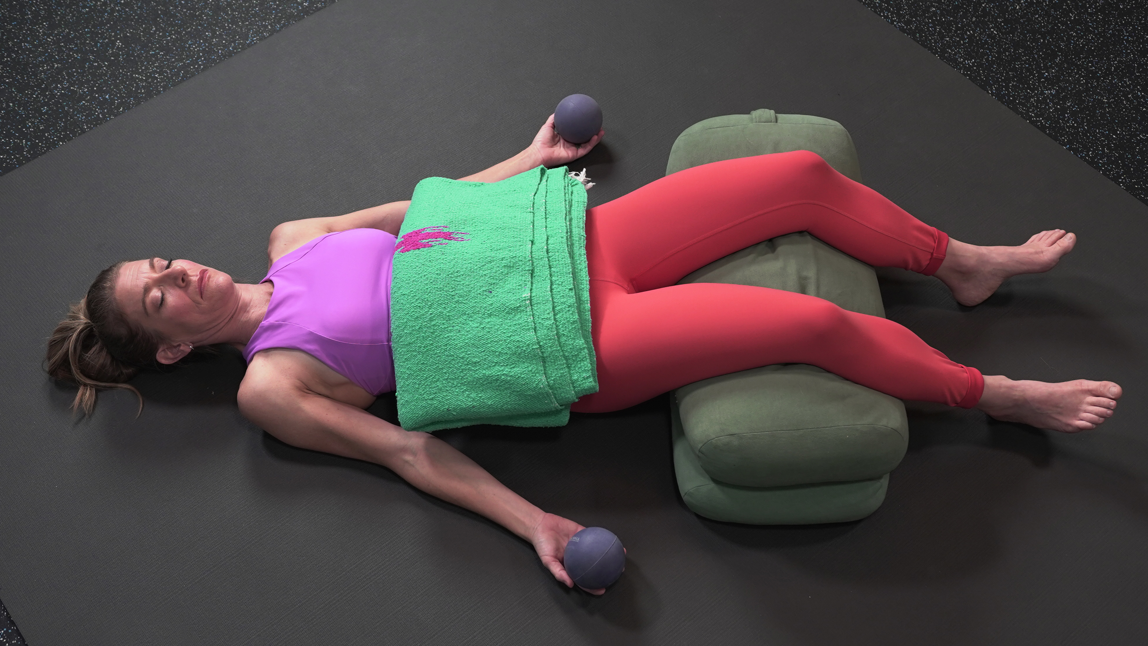 Woman lies in constructive rest position; two yoga bolsters propping up knees, a folded blanket on the abdomen and alpha self massage balls in hand to add weight and comfort